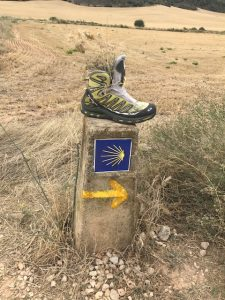 A Camino way marker with a typical 'adornment'